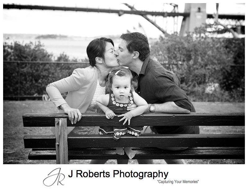 Family portrait of little girls with parents kissing behind her - sydney family portrait photographer